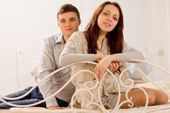 Jeunes couples amicaux attrayants détendant sur un lit Images stock