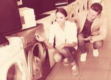 Jeunes couples amicaux choisissant la machine à laver dans l'hypermarché Photo libre de droits