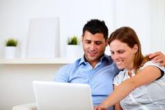 Jeunes couples amicaux utilisant l'ordinateur portatif ensemble Photos libres de droits