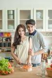 Jeunes couples amoureux de sourire heureux faisant cuire ensemble à la maison Photo stock