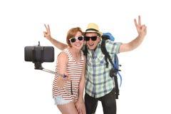 Jeunes couples américains attrayants et chics prenant la photo de selfie avec le téléphone portable d'isolement sur le blanc Images libres de droits