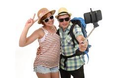Jeunes couples américains attrayants et chics prenant la photo de selfie avec le téléphone portable d'isolement sur le blanc Photos stock