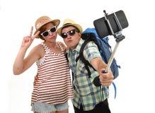 Jeunes couples américains attrayants et chics prenant la photo de selfie avec le téléphone portable d'isolement sur le blanc Photo stock