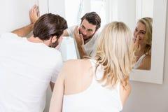 Jeunes couples appliquant la crème sur le visage Photo stock