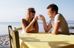 Jeunes couples appréciant des boissons au bord de la mer Photo libre de droits