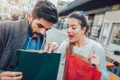 Jeunes couples appréciant en café extérieur après l'achat Photographie stock