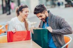 Jeunes couples appréciant en café extérieur après l'achat Images stock