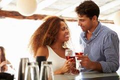 Jeunes couples appréciant la boisson à la barre extérieure Photographie stock libre de droits