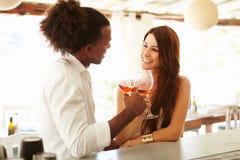 Jeunes couples appréciant la boisson à la barre extérieure Photos stock