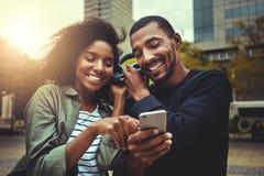 Jeunes couples appréciant la musique sur l'écouteur sans fil photos stock