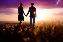 Jeunes couples appréciant le coucher du soleil Image stock