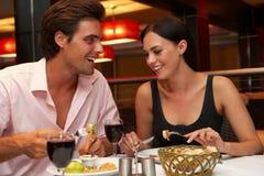 Jeunes couples appréciant le repas dans le restaurant Images libres de droits