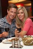Jeunes couples appréciant le repas dans le restaurant Photo stock