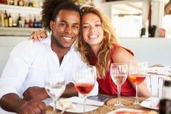 Jeunes couples appréciant le repas dans le restaurant extérieur Images stock