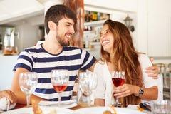 Jeunes couples appréciant le repas dans le restaurant extérieur Photographie stock libre de droits