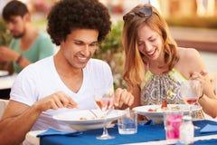 Jeunes couples appréciant le repas dans le restaurant extérieur Photographie stock