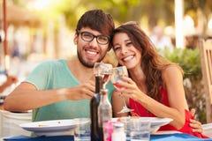 Jeunes couples appréciant le repas dans le restaurant extérieur Photo stock