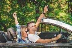 Jeunes couples appréciant le voyage par la route avec des mains à l'intérieur de leur voiture convertible Photos stock