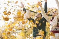 Jeunes couples appréciant les feuilles d'automne en baisse en parc photographie stock