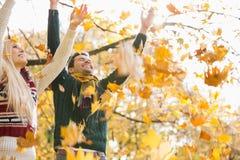 Jeunes couples appréciant les feuilles d'automne en baisse en parc Images stock