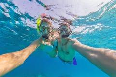 Jeunes couples appréciant naviguer au schnorchel sous l'eau portrait de selfie Image stock