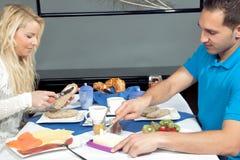 Jeunes couples appréciant un petit déjeuner chaleureux Photo stock