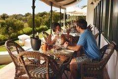 Jeunes couples appréciant un verre de vin au restaurant d'établissement vinicole Photographie stock libre de droits