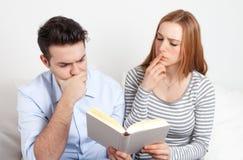 Jeunes couples apprenant avec un livre Photos libres de droits
