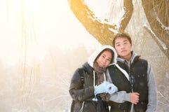 Jeunes couples asiatiques dans la chute de neige d'hiver Images stock