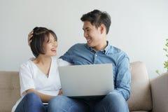 Jeunes couples asiatiques faire l'amusement de travailler à l'ordinateur portable ils se reposent sur le sofa dans le salon conte photos stock