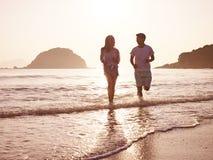 Jeunes couples asiatiques fonctionnant sur la plage Photo stock