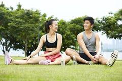 Jeunes couples asiatiques parlant tout en s'exerçant Photographie stock