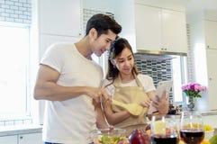 Jeunes couples asiatiques semblant comment à la cuisson sur le comprimé Photo stock