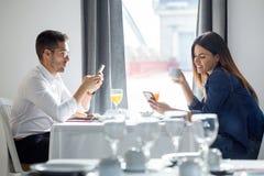 Jeunes couples assidus utilisant leur téléphone portable dans la salle à manger de l'hôtel photo libre de droits