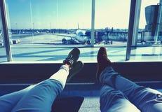 Jeunes couples attendant l'avion à un aéroport jambes d'humains avec l'avion sur le fond Photos stock