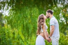 Jeunes couples attendant le bébé en parc d'été Images stock