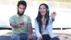 Jeunes couples attrayants écoutant la musique avec des écouteurs et la danse banque de vidéos