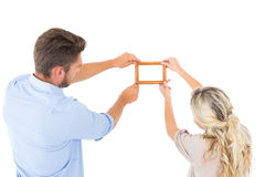Jeunes couples attrayants accrochant un cadre Image libre de droits