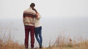 Jeunes couples attrayants dans des chandails tricotés sur une falaise sur le bord de mer, taquiner, étreindre et embrasser banque de vidéos