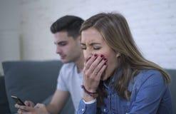 Jeunes couples attrayants dans le problème de relations avec l'ami de dépendance de téléphone portable d'Internet ignorant le gi  Images libres de droits