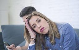 Jeunes couples attrayants dans le problème de relations avec l'ami de dépendance de téléphone portable d'Internet ignorant le gi  Photo stock