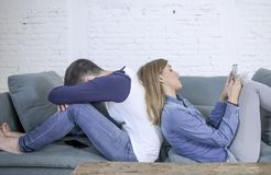 Jeunes couples attrayants dans le problème de relations avec l'amie de dépendance de téléphone portable d'Internet ignorant b nég image stock