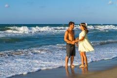 Jeunes couples attrayants dans le tenue de plage à la plage Photo stock