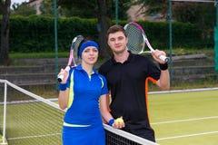 Jeunes couples attrayants des joueurs de tennis tenant une raquette et Photos libres de droits