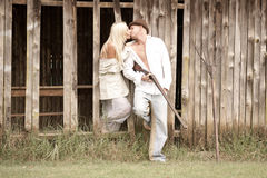 Jeunes couples attrayants embrassant contre le mur en bois de grange Images stock
