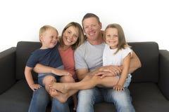 Jeunes couples attrayants et heureux posant reposant à la maison le sofa Co Image stock