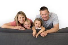 Jeunes couples attrayants et heureux posant reposant à la maison le sofa Co Images libres de droits