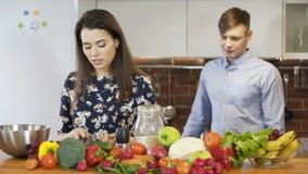 Jeunes couples attrayants faisant cuire dans la cuisine et appréciant ensemble clips vidéos