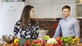 Jeunes couples attrayants faisant cuire et causant dans la cuisine banque de vidéos