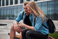 Jeunes couples attrayants heureux dans des vêtements sport se reposant sur un banc contre un gratte-ciel, observant quelque chose Images stock